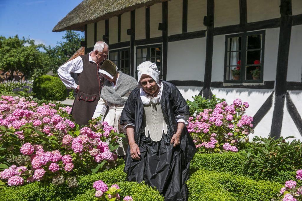 To personer klædt i gamle dragter foran Skovridergården