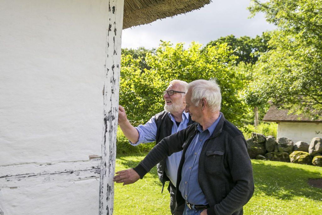 2 mænd ser nærmere på et hus i De gamle huse