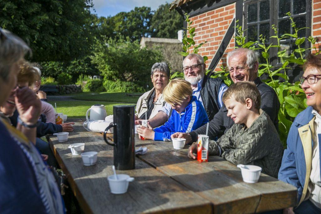 Familie ved borde og bænke med kaffe