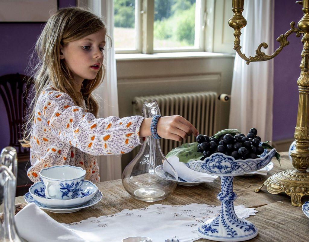 Pige tager druer på et fad