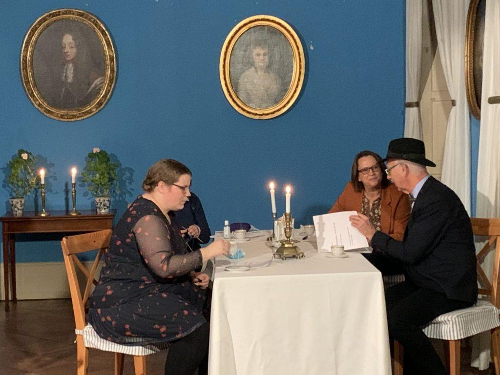 En familie sidder rundt om et bord på herregården til et arrangement