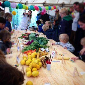 Bord med mad på og mange glade børn og voksne