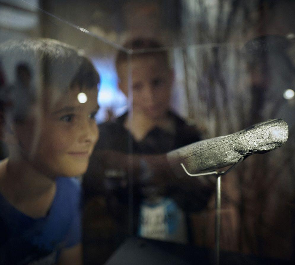 Børn kigger på genstand i Lola udstillingen